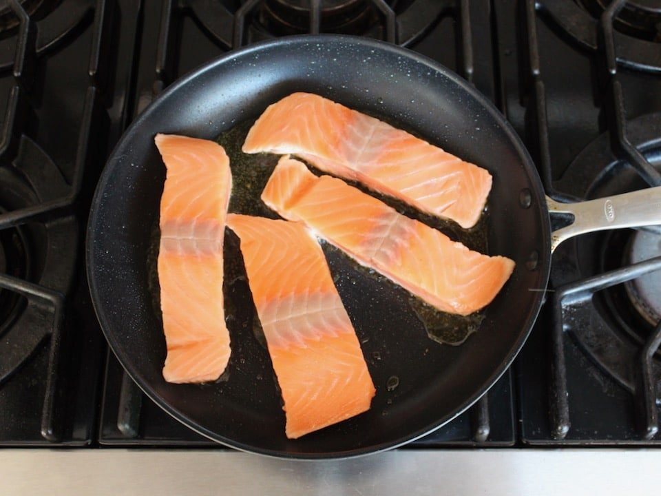Four skinless salmon fillets face-down in a skillet on stovetop.