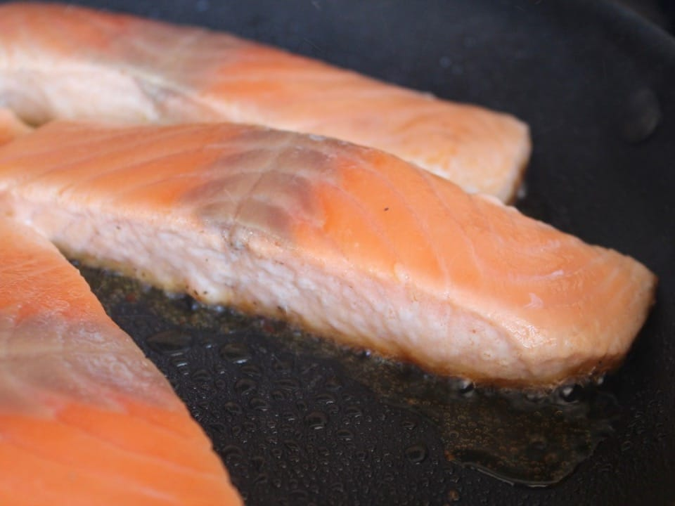Skinless salmon fillets searing in skillet, close up of bottom of fillet as it begins to brown.
