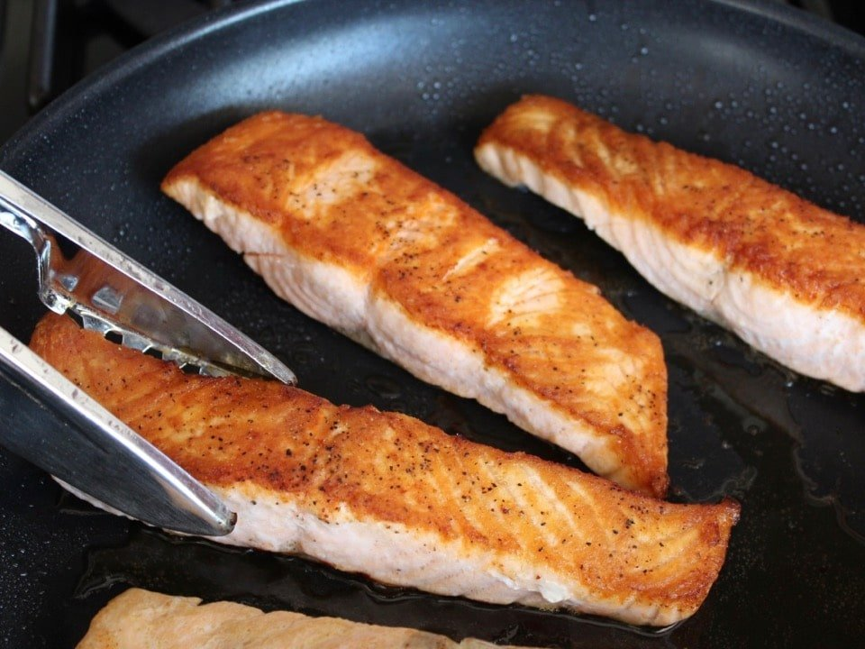 Tongs turning salmon fillet in skillet of seared crispy golden fillets.