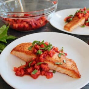 Square Crop - seared salmon fillet topped with macerated strawberry balsamic sauce and fresh basil chiffonade, another plate of the same entree in background, with a glass bowl of macerating strawberries and a pile of fresh basil in the back.