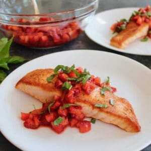 Horizontal Crop - seared salmon fillet topped with macerated strawberry balsamic sauce and fresh basil chiffonade, another plate of the same entree in background, with a glass bowl of macerating strawberries and a pile of fresh basil in the back.