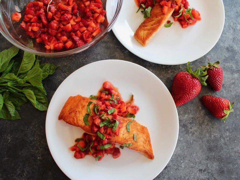 Overhead shot - plate of seared salmon topped with strawberry sauce and chopped basil, another plate nearby, bowl of macerating strawberries, fresh basil on the table with whole strawberries nearby.