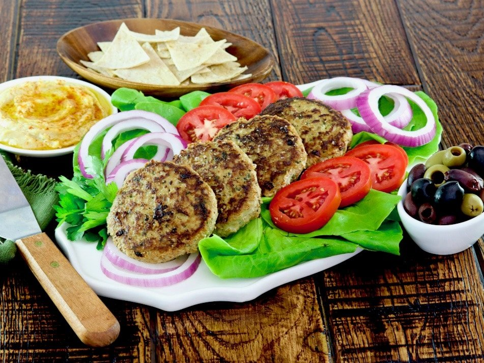 Wide horizontal shot - white plate of four turkey burgers stacked in a line garnished with lettuce, red onion and tomato slices with a dish of olives, hummus, and pita chips on the side, spatula laying nearby on wooden table.