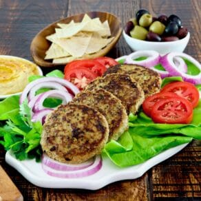 Square Crop - Plate with four grilled Mediterranean Turkey Burgers with onion slices, tomato slices and a bed of fresh green lettuce. Hummus, pita chips, and a dish of olives in the background.