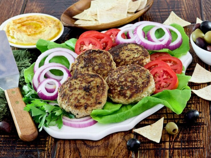 Horizontal Shot - plate with four grilled Mediterranean Turkey Burgers with onion slices, tomato slices and a bed of fresh green lettuce. Hummus, pita chips, and a dish of olives in the background.