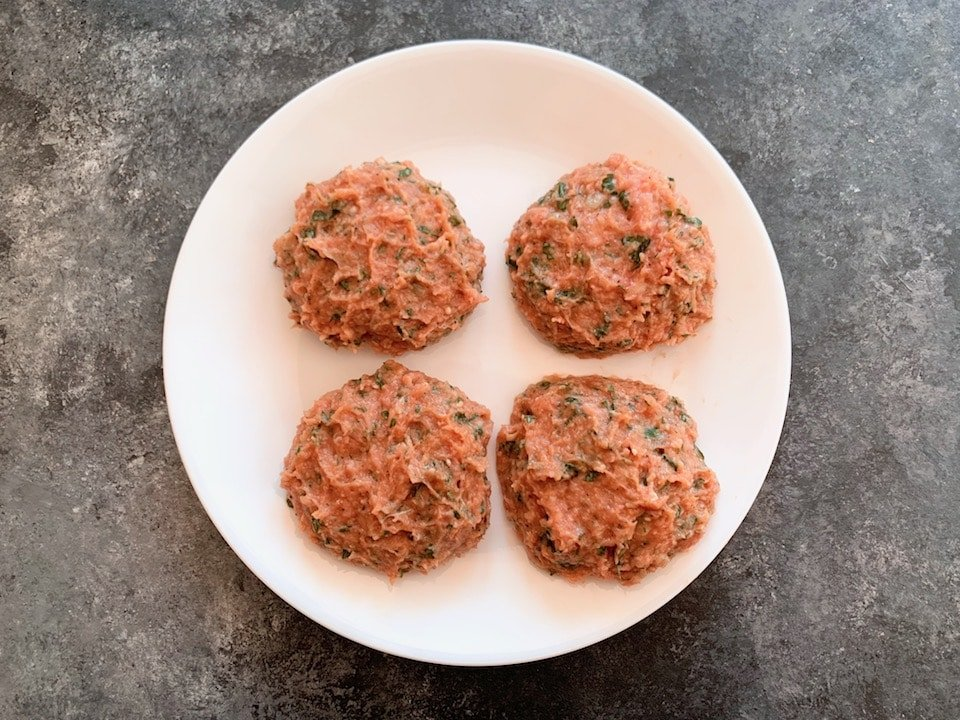 Four soft turkey burger patties loosely formed, uncooked on white plate, grey surface beneath.