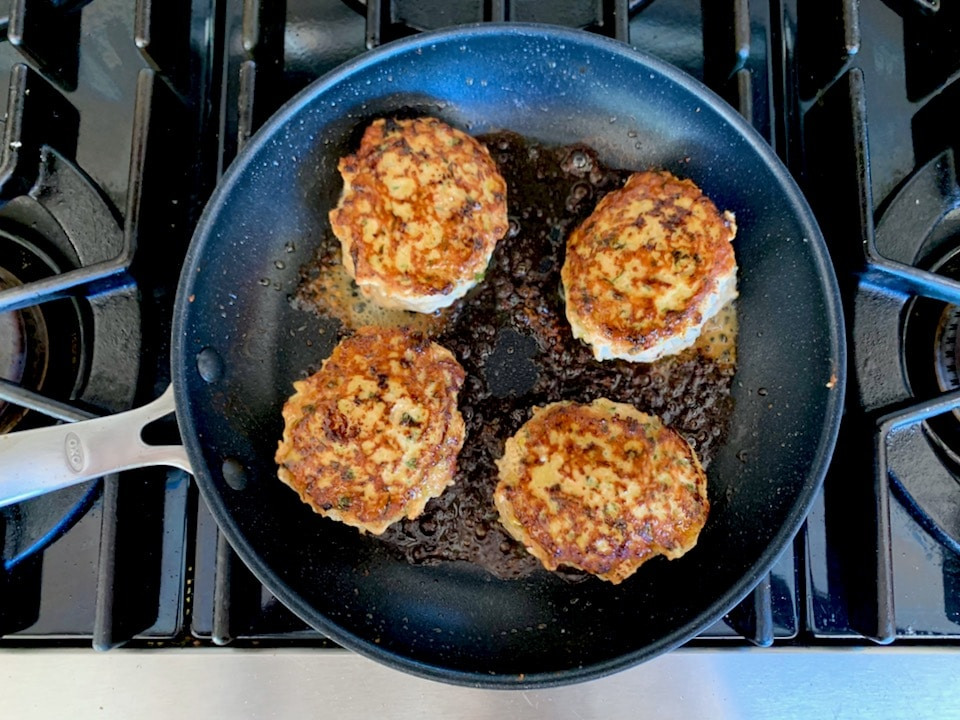 Four turkey burger patties cooking in a nonstick skillet, sizzling with olive oil on stovetop.