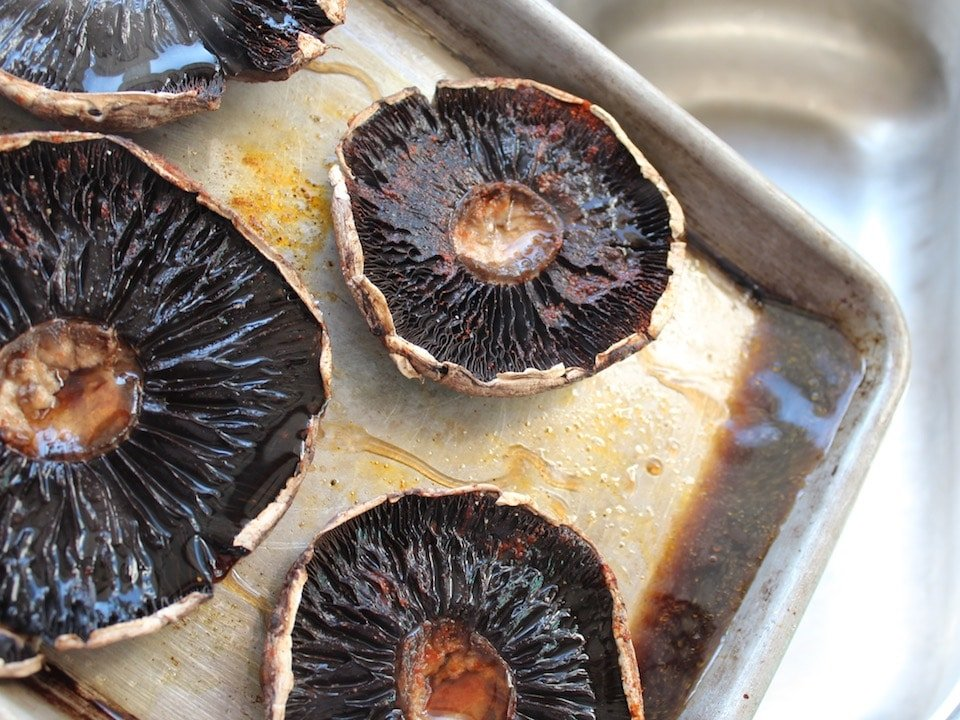 Pouring excess liquid off a baking sheet with roasted portobello caps.