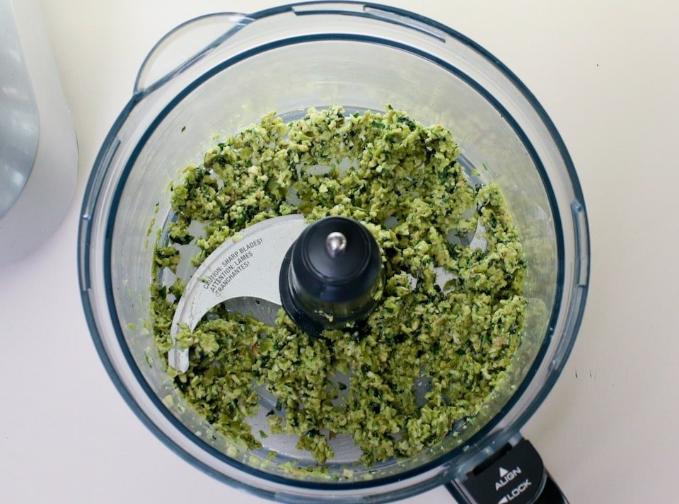 Overhead shot of food processor bowl filled with green tapenade.