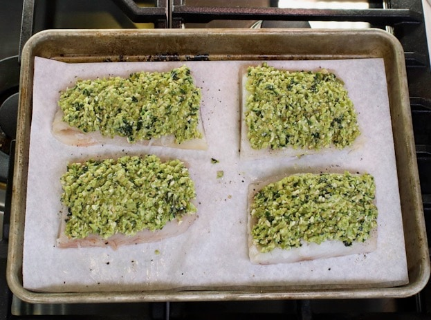 Sheet pan with four raw whitefish fillets topped with basil tapenade.