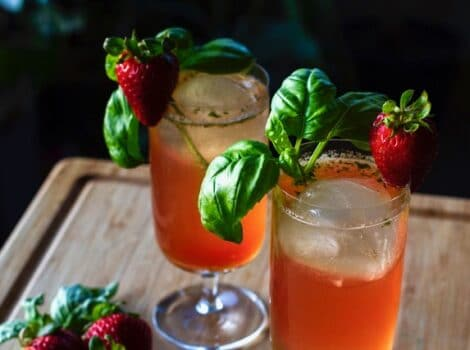 Two cocktail glasses filled with a red beverage and garnished with a sprig of basil and a strawberry.