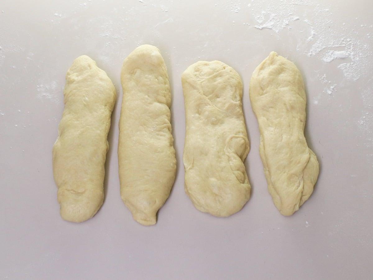 Overhead shot of challah dough separated into 4 rectangular pieces.