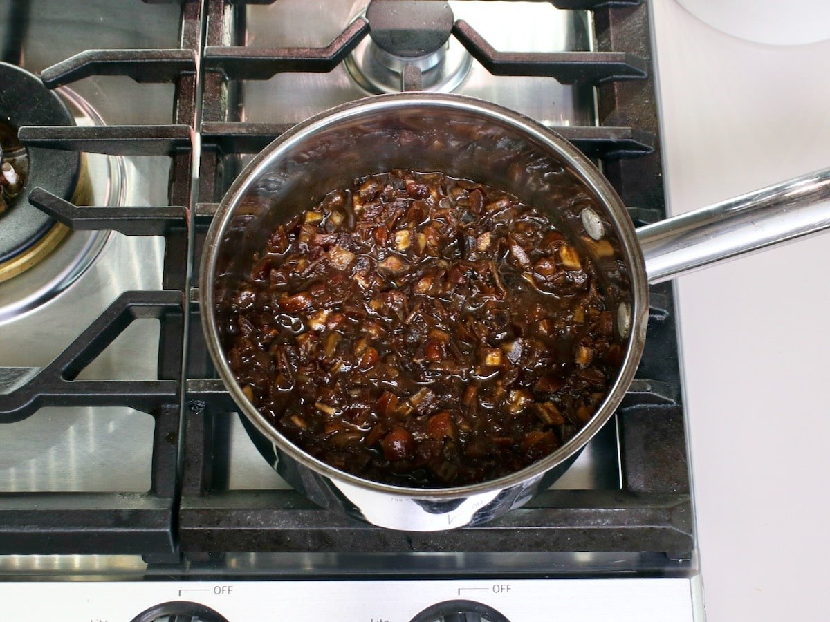 Saucepan filled with bubbling date filling on the stovetop.